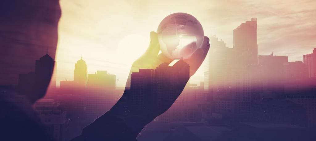 Business man in suit with cityscape montage. The man is unrecognizable and you cannot see his face. He is superimposed onto a city skyline at sunset. He is holding a world map globe like a crystal ball. Success, vison concept with copy space.