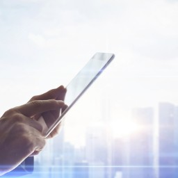 Hands with digital tablet on blurred city background